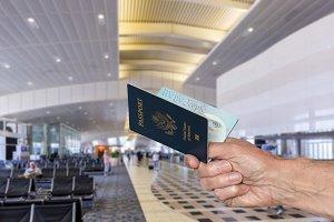 Senior arm holding US Passport at airport terminal