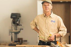 Senior caucasian man in home workshop with voting sticker
