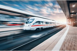 White modern high speed train in motion on railway station at su