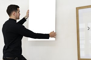Man hanging painting on a wall (PNG)