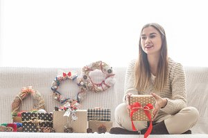 girl with Christmas gifts sitting on the sofa