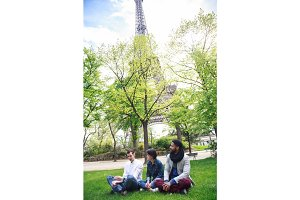 Multi-ethnic Group Of Friends Having Fun In Park Near Eiffel