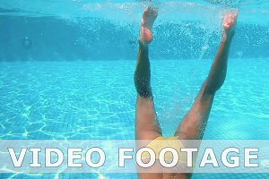 Beautiful woman is diving underwater in water pool
