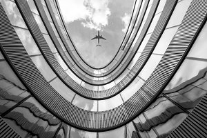 Flying airplane over modern building