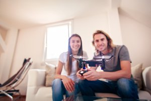 Young Couple Playing With A Small Quadrocopter Drone
