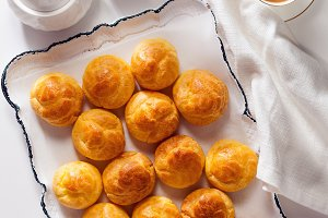 profiteroles and coffee on white trey for sweets . utensils for