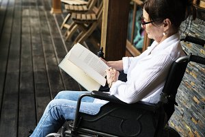 Woman sit on wheelchair and read