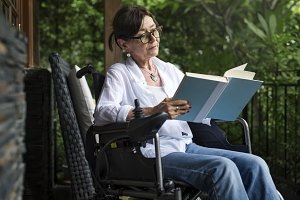 Woman reading a book in a wheelchair