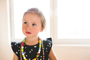 Cute little girl in dress at home wearing red lipstick.