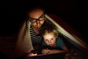 Father with tablet and little daughter at home at night.