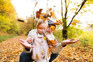 Young father with his daughter in autumn forest.