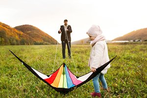 Father with little daughter with kite. Autumn nature.