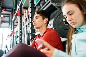 Fit couple in modern crossfit gym with smartphone.