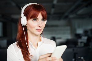 Businesswoman with earphones and smartphone.