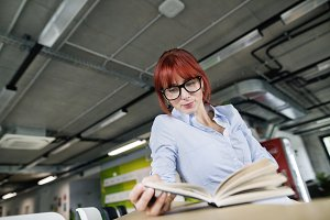 Businesswoman with a book in her office working.
