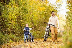 Father with little son cycling in autumn park.