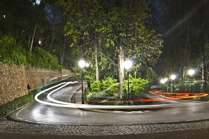 curve road at night in the forest of the Alhambra with trailing lights taxi