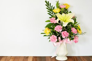 Bouquet of flowers in vase on wooden table