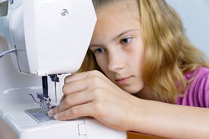 The teenage girl carefully inserts the thread in the needle
