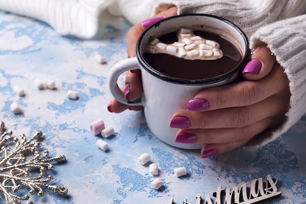 female hand holding cup of hot coco…