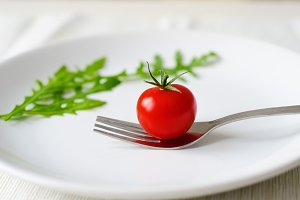 Tomato with arugula on white plate
