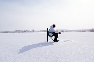winter fisherman on frozen lake