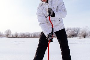 winter fisherman with ice screw