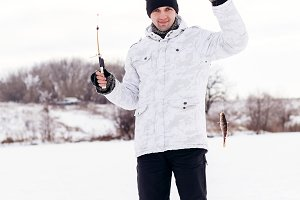 winter fisherman with jig and fish