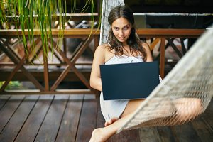 woman lying in a hammock with laptop