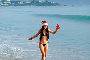 sexy santa woman on beach present