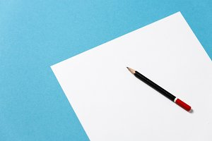 Black pencil lies on a clean white sheet of paper on a blue background, top view, creative office space minimalism concept