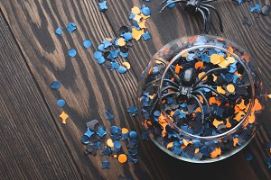 Halloween party confetti and spiders on dark