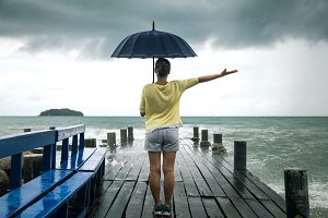 a young girl on a pier with an umbrella