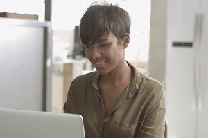 Cute young black woman in loft style office