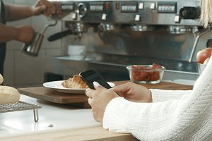 Attractive young woman wearing a white sweater in a loft style bakery or coffee shop with a movile phone