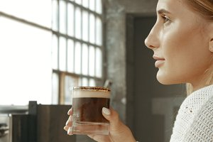 Attractive young woman wearing a white sweater in a loft style bakery or coffee shop with an ice latte