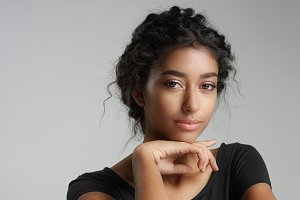 Attractive young Middle Eastern model touching her pretty face with flawless skin.