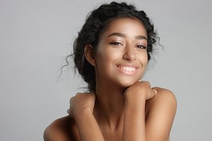 happy serene young woman with beautiful olive skin and curly hair ideal skin and brown eyes in studio