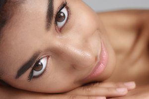 Close up shot of a pretty young wooman with smooth glowing skin relaxing on a white massage table.
