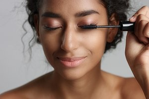 Adorable teenage Middle Eastern girl with great skin applying mascara to her long lashes