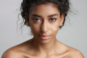 middle eastern young woman in studio with a foundation on cheek closeup Touching skin