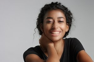 young girl with perfect light brown skin and beautiful curly black hair smiling at the camera