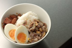 Serving Asian style soup with rice, pork, hardboiled egg and eggplant
