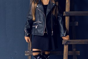 baby girl with long hair in leather jacket standing