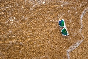 sunglasses with a white rim and mirror lenses in the sea water covered with a wave on the yellow clean sand