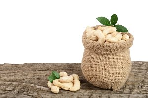 cashew nuts with leaf in bag on wooden table with white background