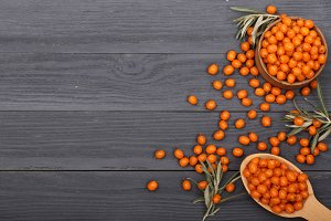 Sea buckthorn. Ripe fresh berries in bowl on black wooden background with copy space for your text. Top view