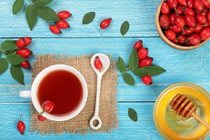 tea with rose hips and honey on blue wooden background. Top view