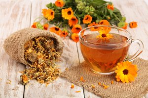 Calendula tea with fresh and dried flowers on white wooden background