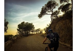 cyclist man riding a mountain bike at sunset mountain tibidabo in Spain city of Barcelona